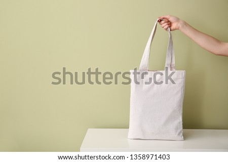 Female hand with eco bag on table against color background #1358971403
