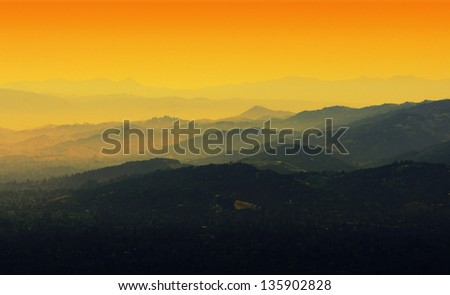 Layers of distant mountains in morning mist and a dramatically colored sky. This photo was taken from a nature hike in the Santa Cruz Mountains to the south of the San Francisco Bay Area.