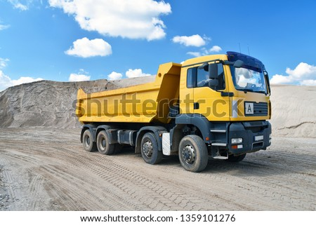 Truck transports sand in a gravel pit - gravel mining in an open pit mine  #1359101276