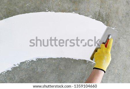 Hand with a spatula, the process of applying a layer of putty. Renovation of apartments. Repair the walls. Free space for advertising, text. #1359104660