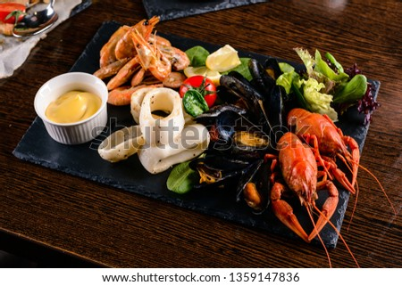 Seafood platter. Mediterranean cuisine restaurant food, fried calamari rings, king prawns, mussels, oysters, shellfish delicacy, top view on wood table background. Catering, banquet table #1359147836