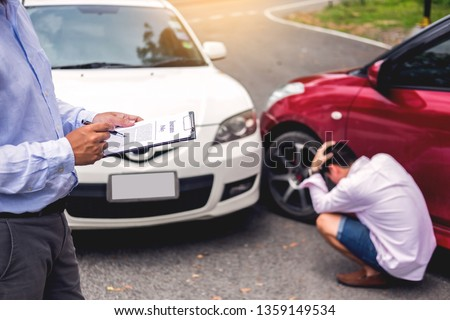 Insurance agent writing on clipboard while examining car after accident claim being assessed and processed #1359149534