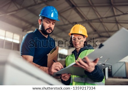 Factory worker signing document in industrial hall #1359217334