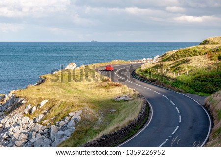 The eastern coast of Northern Ireland and Antrim Coastal Road, a.k.a. Causeway Coastal Route with a red car sunset light #1359226952
