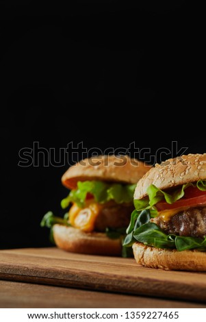 selective focus of delicious meat burgers with cheese and sesame isolated on black #1359227465
