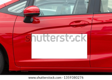 Horizontal shot of a blank white magnetic sign on a red car's driver side door.