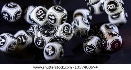 Black and white lottery balls in a bingo machine. Lottery balls in a sphere in motion. Gambling machine and euqipment. Blurred lottery balls in a lotto machine. #1359400694