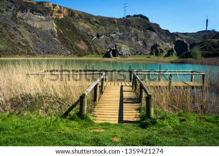 wooden walkway next to a lake during spring, la arboleda, basque country #1359421274