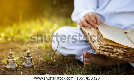 Buddhist  monk sits in  yoga lotus position meditating, reading old open book of wisdom, and there are a number  Tibetan bells and burn incense at meadow. beautiful sunset background #1359453323