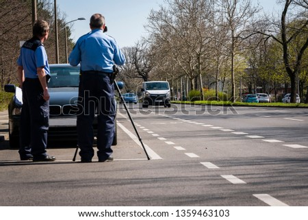 Police makes a Speed Control, Speed Control with Laser Pistol, Radar, Police at Work, Traffic Check, Germany, Berlin, German Police, Police Officer #1359463103