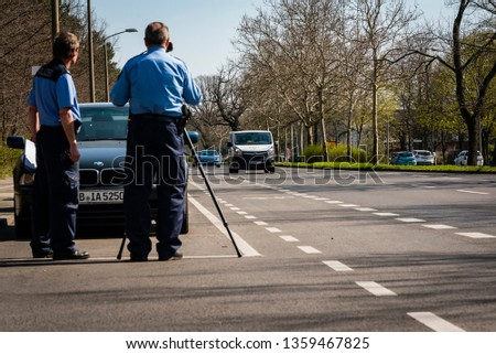 Berlin/Germany - April 4 2019: Police makes a Speed Control, Speed Control with Laser Pistol, Radar, Police at Work, Traffic Check, Germany, Berlin, German Police, Police Officer #1359467825