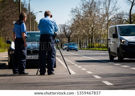 Berlin/Germany - April 4 2019: Police makes a Speed Control, Speed Control with Laser Pistol, Radar, Police at Work, Traffic Check, Germany, Berlin, German Police, Police Officer #1359467837
