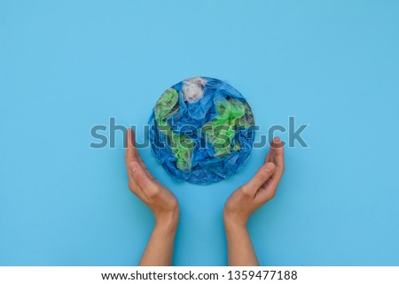 Hands holding planet Earth made from plastic disposable packages on blue background. Save the world, creative, environment pollution or World Earth Day concept. Top view #1359477188