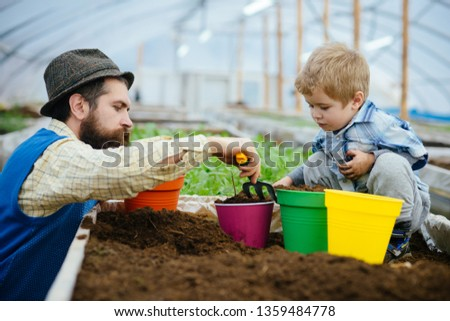 father and son in greenhouse. father and son in greenhouse planting together. father and son working together in greenhouse. son and father have fun in greenhouse. good day for gardening #1359484778