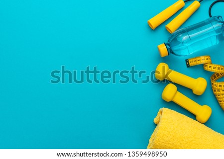 flat lay photo of fitness equipment over turquoise blue backgound. top view of yellow street workout objects. yellow fitness objects on the blue background with some copy space #1359498950
