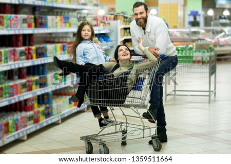 Beautiful young parents and their cute little daughter are smiling while choosing food in the supermarket. Father pushes the shopping cart while the girls sit there #1359511664