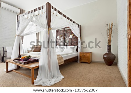 Hotel room - vacation concept background - Luxurious modern bedroom interior with canopy bed Royalty-Free Stock Photo #1359562307