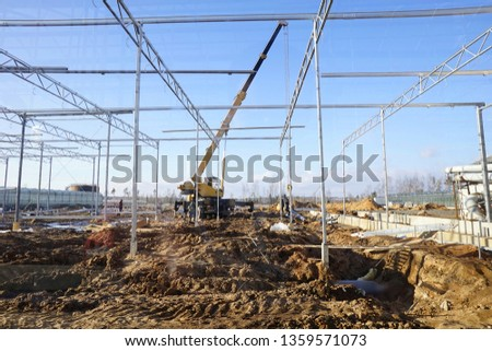 greenhouses under construction from metal structures and glass with communications for growing vegetables and flowers #1359571073