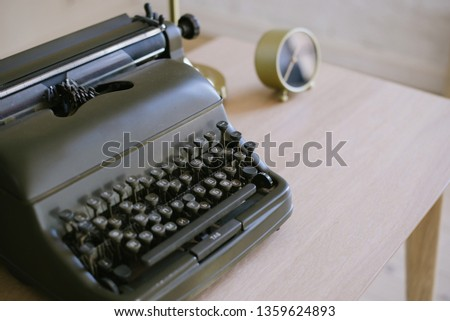 Antique typewriter on a wooden table background with papers ready for a new book or a novel with many failing pages lined up on a desktop. office equipment. clock, pencil, flowers  #1359624893