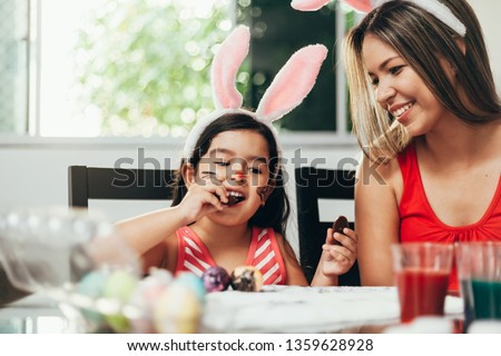 Happy easter! A mother and her daughter painting Easter eggs. Happy family preparing for Easter. Cute little child girl wearing bunny ears on Easter day #1359628928