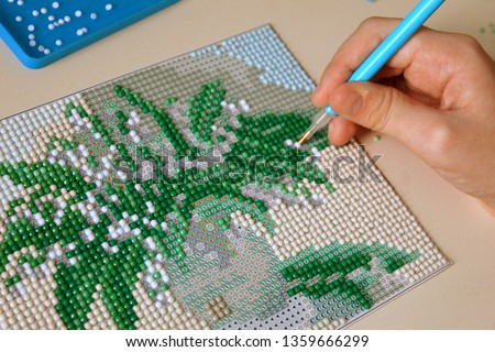 The process of creating a diamond mosaic of a picture of a vase with spring branches, selective focus.