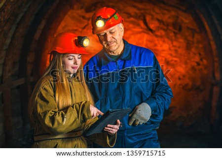 A beautiful young girl in a red helmet and with a electronic tablet in her hands is standing with a miner in a coal mine. Business plan discussion. #1359715715