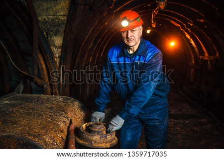 A miner in a coal mine stands near a trolley. Copy space. #1359717035
