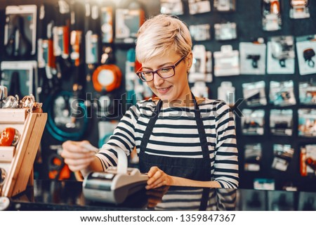 Smiling Caucasian female worker with short blonde hair and eyeglasses using cash register while standing in bicycle store. #1359847367