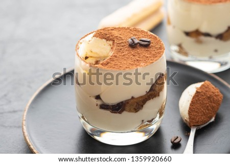 Delicious Italian dessert tiramisu, chocolate, cocoa and coffee beans on a black background. Copy space. #1359920660
