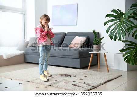 Little girl in muddy shoes messing up carpet at home #1359935735