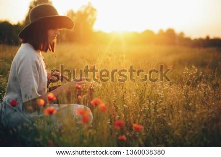 Stylish girl in linen dress gathering flowers in rustic straw basket, sitting in poppy meadow in sunset. Boho woman in hat relaxing in warm evening sunlight in summer field. Space for text #1360038380