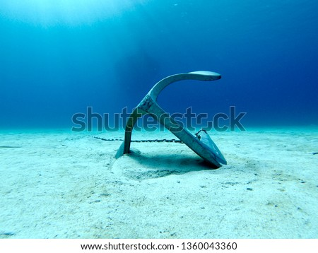 an anchor lying on the sand in the crystal blue water of the Mediterranean off the coast of minorca.