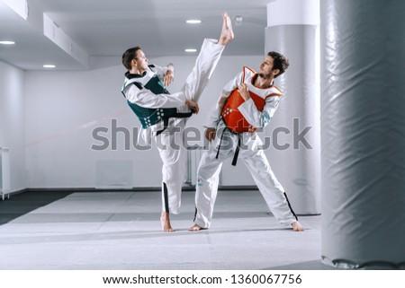 Two Caucasian sporty men sparring in tekwondo fittings barefoot. #1360067756