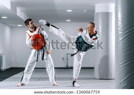 Two Caucasian sporty men sparring in tekwondo fittings in gym with bucklers on. #1360067759