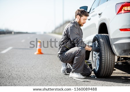 Handsome road assistance worker in uniform changing car wheel on the highway Royalty-Free Stock Photo #1360089488