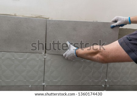 The hands of the tiler are laying the ceramic tile on the wall. Horizontal image. Close up. #1360174430