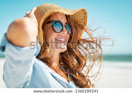 Side view of beautiful mature woman wearing sunglasses at beach. Young smiling woman on vacation looking away while enjoying sea breeze wearing straw hat. Closeup portrait of attractive girl relaxing. #1360189241