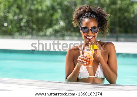 Portrait of happy fashion woman with sunglasses standing in swimming pool drinking cocktail. Beautiful african glamour girl with fresh soft drink for appetizer in luxury pool looking at camera. #1360189274