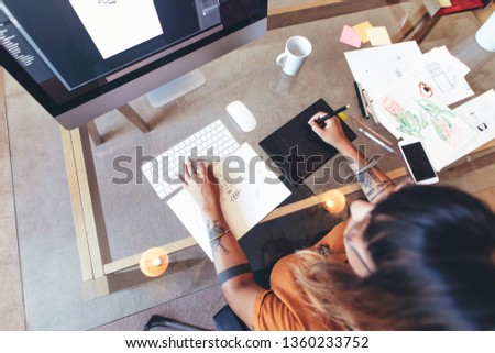 Top view of an illustrator making creative designs on a computer. Female artist using a digital writing pad to make an illustration on a computer. Royalty-Free Stock Photo #1360233752