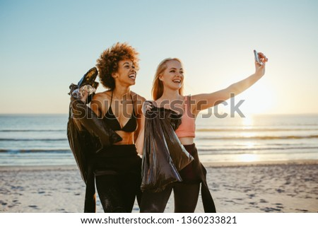Two young women holding garbage bags and taking selfie after cleaning the beach area. Two girls tidying up rubbish on beach and taking a selfie. #1360233821
