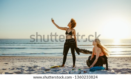 Woman taking selfie with her friend while cleaning the beach area. Two girls tidying up rubbish on beach and taking a selfie. #1360233824