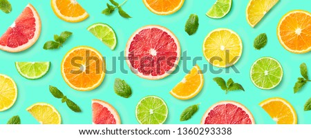 Colorful pattern of citrus fruit slices and mint leaves on blue background. Top view, flat lay #1360293338