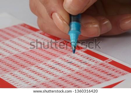 woman Hand Playing Turkish Lottery .(Turkish Sayisal Loto, Super loto, Sans topu, on numara game) #1360316420
