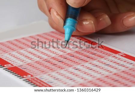 woman Hand Playing Turkish Lottery .(Turkish Sayisal Loto, Super loto, Sans topu, on numara game) #1360316429