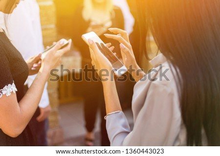 Couple friends holding smart phone on hand. Back view of young girl holding smart phone #1360443023