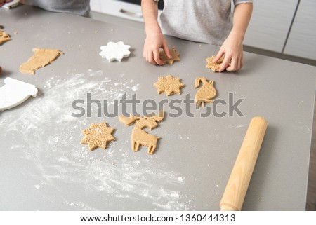 The gray table is filled with flour; the child molds dough with cookie cutters. #1360444313
