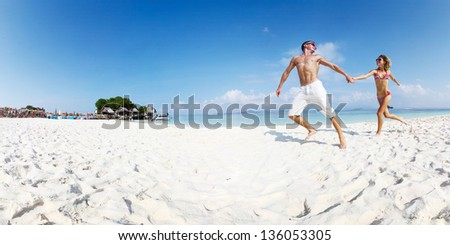 Panorama with young happy couple running on a sandy beach of tropical island at sunny day #136053305