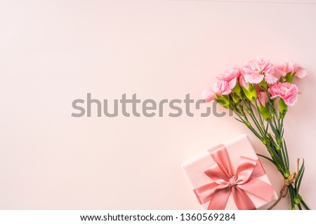 mothers day design concept - top view of a bunch of carnation, gift box on pink background for wedding and valentines day with copy space for mock up #1360569284