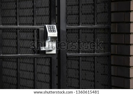 Keypad lock on an exterior garden gate, in a security background with space for text Royalty-Free Stock Photo #1360615481