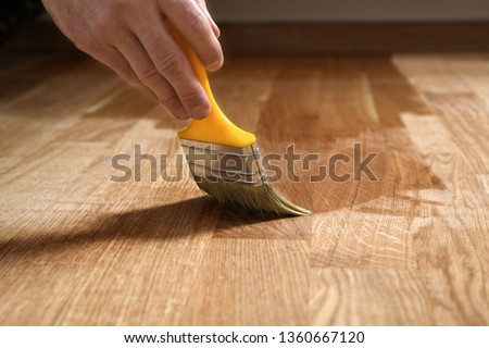 Varnishing lacquering parquet floor by paintbrush - second layer. Home renovation parquet. Varnish paintbrush strokes on a wooden parquet. Application of a highly glossy parquet lacquer #1360667120